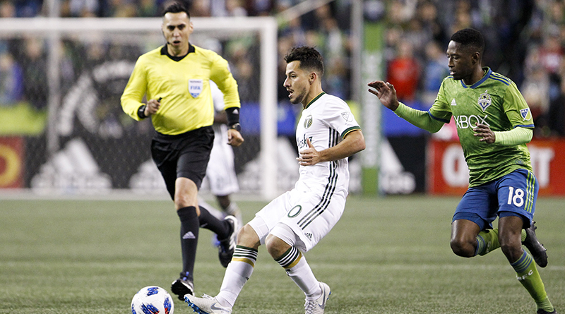 Jair Marrufo looks on as Portland Timbers midfielder Sebastian Blanco (10) passes the ball away from pressure by Seattle Sounders defender Kelvin Leerdam (18) during the second half at CenturyLink Field.