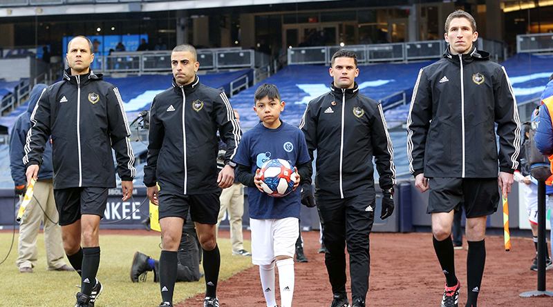 The officials and game ball are escorted to the pitch by a young fan before a game between New York City FC and D.C. United at Yankee Stadium.