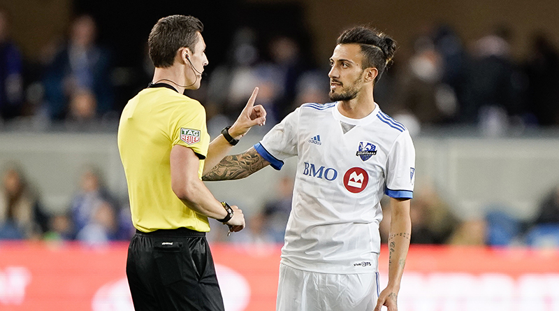 Montreal Impact forward Maximiliano Urruti receives a warning from Joe Dickerson.