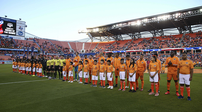 Columbus Crew and Houston Dynamo players stand on the field with children, alongside the PRO crew before a game at BBVA Compass Stadium.