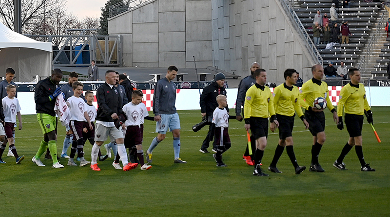 D.C. United and Colorado Rapids players accompany youngsters onto the field before the game at Dick's Sporting Goods Park.