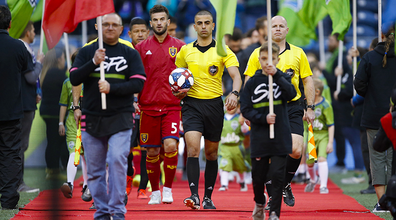 Head referee Nima Saghafi leads the teams onto the field before the start of a game between the Seattle Sounders FC and Real Salt Lake at CenturyLink Field.