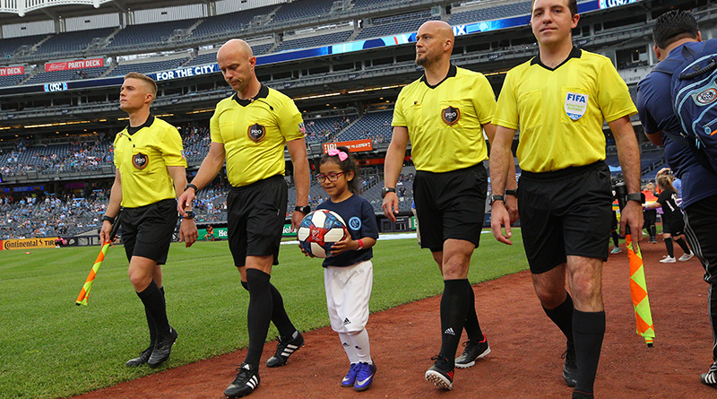 A young fan delivers the game ball with the officials before a game between New York City FC and FC Cincinnati at Yankee Stadium.