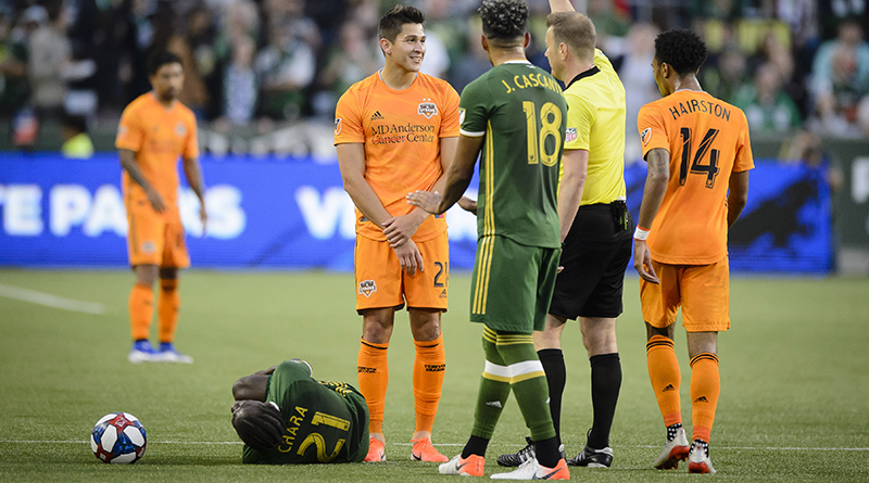 Houston Dynamo forward Ronaldo Pena (21) receives a yellow card after a challenge on Portland Timbers midfielder Diego Chara (21) during the first half at Providence Park.