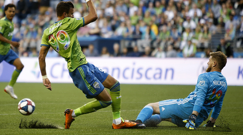 Seattle Sounders forward Justin Dhillon (99) fouls Vancouver Whitecaps goalkeeper Zac MacMath (18) during the second half at CenturyLink Field. The foul would result in a no goal call against the Sounders.