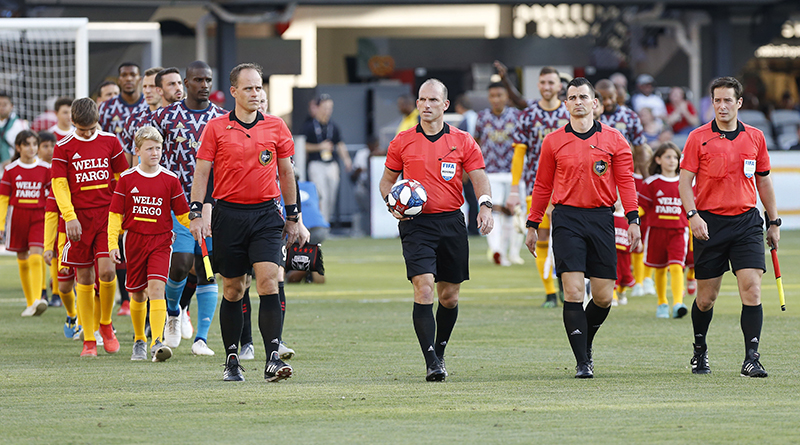 Referee Ted Unkel (holding ball) leads his crew and the teams onto the pitch prior to the match between D.C. United and New England Revolution match at Audi Field.
