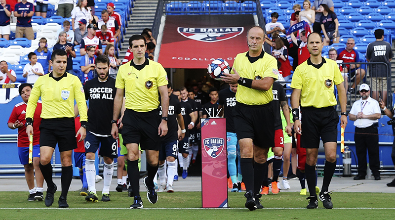 Officials walk onto the pitch before the match between the Vancouver Whitecaps and FC Dallas at Toyota Stadium.