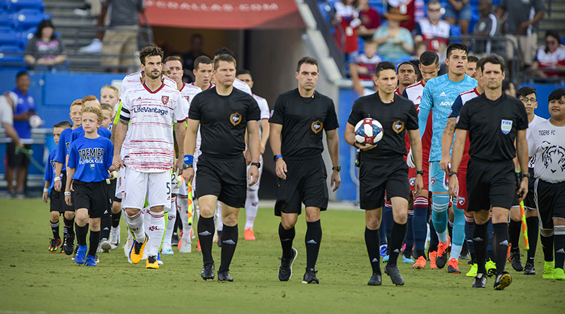 Real Salt Lake and FC Dallas walk onto the field with their fan escorts before the game at Toyota Stadium.