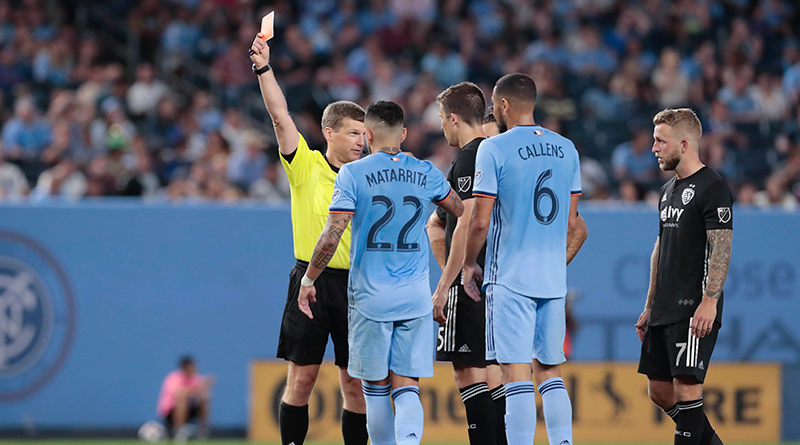 Referee David Gantar explains his decision to issue a red card to Sporting Kansas City midfielder Roger Espinoza to SKC captain Matt Besler during the second half at Yankee Stadium.