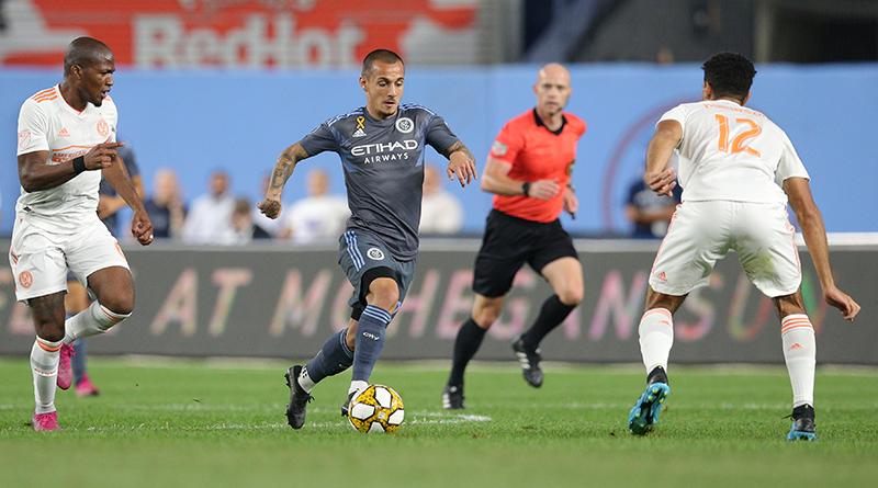 Allen Chapman looks on as New York City FC forward Alexandru Mitrita (28) plays the ball against Atlanta United midfielder Darlington Nagbe (6) and defender Miles Robinson (12) during the first half at Yankee Stadium.