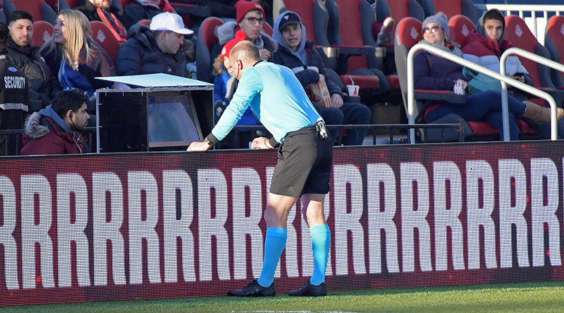 MLS referee Ted Unkel consults a fieldside monitor before disallowing a goal by Toronto FC against New York City in the first half at BMO Field.