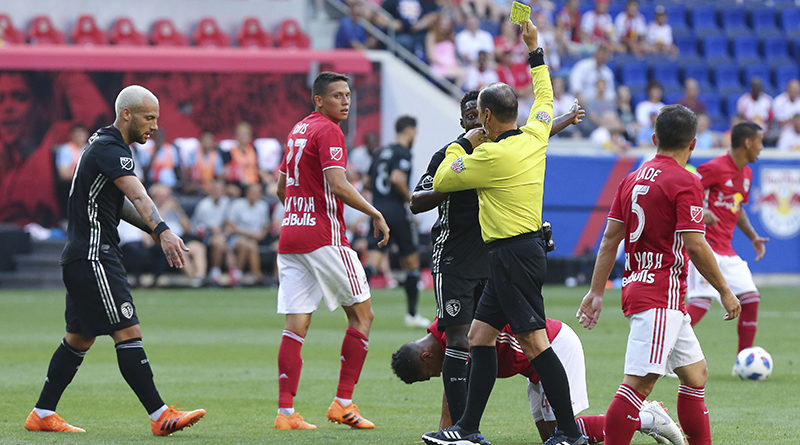 Referee Kevin Stott issues a yellow card to Sporting Kansas City midfielder Yohan Croizet (10) in front of New York Red Bulls midfielder Sean Davis (27) and defender Connor Lade (5) during the first half at Red Bull Arena.