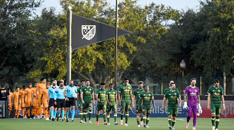 Members of the Portland Timbers and Houston Dynamo teams walk on the field prior to a game at ESPN Wide World of Sports.