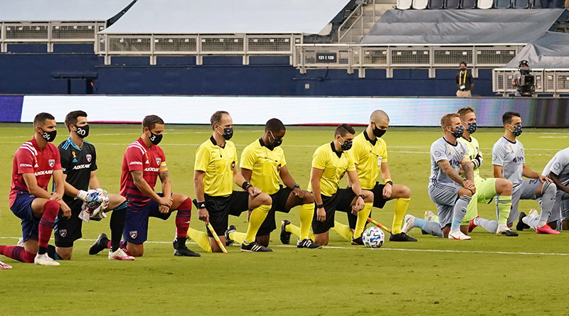 Sporting Kansas City, FC Dallas, and officials kneel and some raise fists during the singing of the national anthem before the match against FC Dallas at Children's Mercy Park.