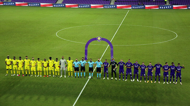 Nashville, Orlando City and referees stand with arms connected during the national anthem at Orlando City Stadium.