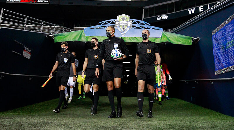 PRO officials lead the teams out onto the field before the start of a game between the Seattle Sounders FC and the Minnesota United at Lumen Field.