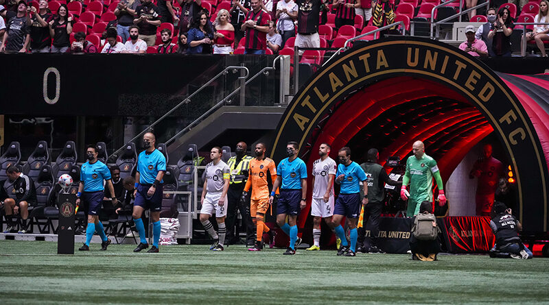 The officials lead the teams of Atlanta United and CF Montreal onto the field at Mercedes-Benz Stadium.