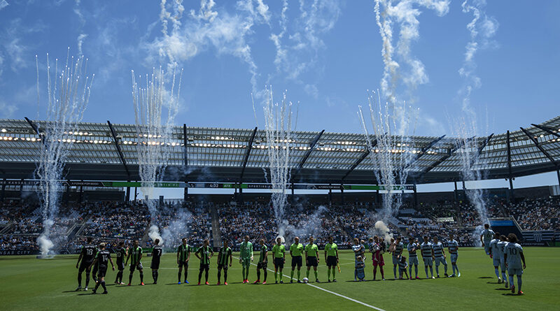 Austin FC and Sporting Kansas City players line up for the national anthem before the match at Children's Mercy Park.